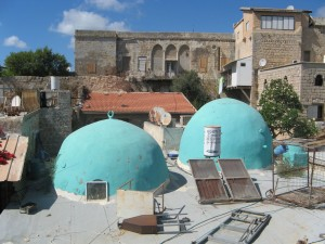 The spunky domes of a neighborhood mosque peep out among rooftop patios and the facades of more stately buildings.